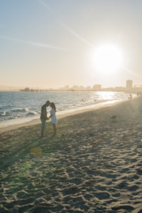 A young couple holds hands and touches foreheads on the beach one late afternoon.