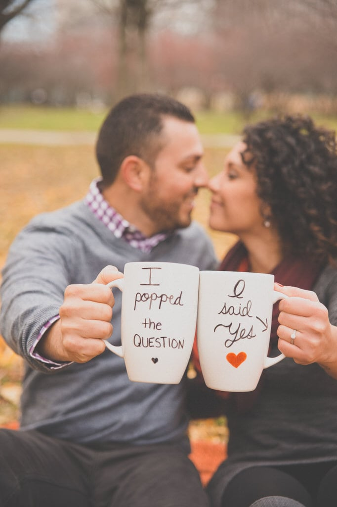 A young couple sits in the park and displays their matching coffee mugs advertising their new engagement.