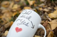 "This fall photograph is personal yet also very romantic. There is a mug laying on a pile of soft yellow leaves with a handwritten message saying ""I said Yes"". That response was obviously associated with someone asking their true love to marry them."