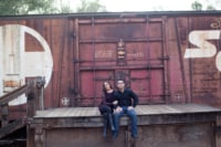 A newly engaged couple sits on a deck next to a freight train.