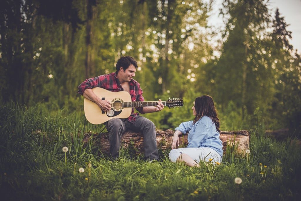 A young couple locks eyes as the man plays his soon-to-be wife a song from his guitar. They are sitting on a log in the middle of the forest with dandelions scattered before them.