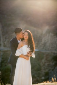A newly engaged young couple takes portrait style photos in the mountain scenery of California. The man holds his fiance around the waist and kisses her cheek.