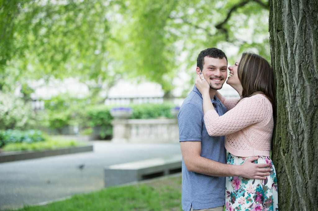 A newly engaged couple smiles and laughs with one another against a large tree in the park.
