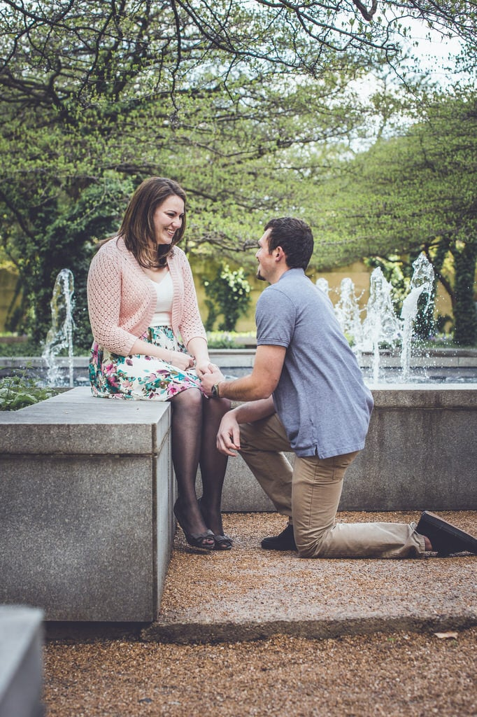 A man kneels on one knee to propose to a woman whilst surrounded by an intricate fountain in a park.
