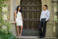 A newly engaged couple stands on either side of an old Victorian style door surrounded by sandstone bricks.