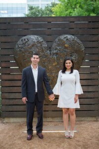 A newly engaged couple holds hands and smiles in front of a large heart sculpture.