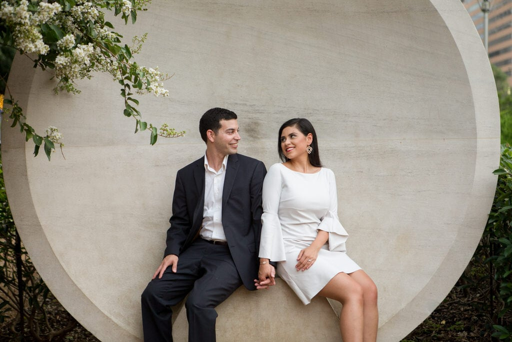 A newly engaged couple sit and hold hands in front of a large, circular sculpture.