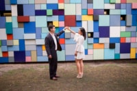 A newly engaged couple smiles and dances in front of a multi-colored, geometric design wall. The woman wears a bell-sleeved, ivory skater dress with taupe, suede, peep-toe wedges.