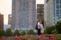 A newly engaged couple shares a kiss in the middle of a colorful city garden surrounded by skyscrapers.