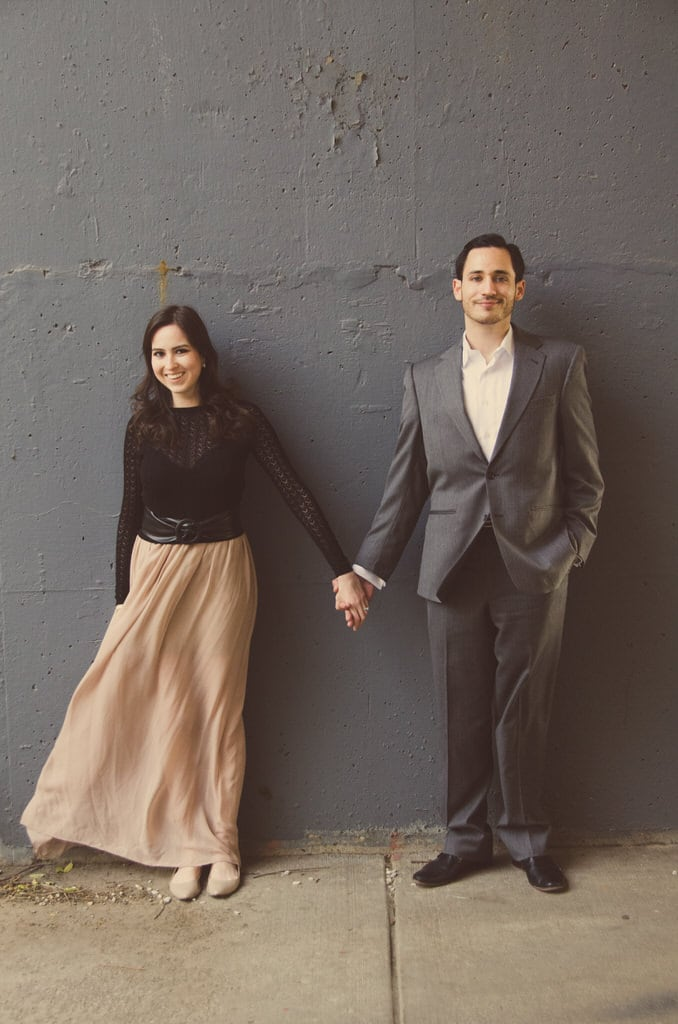 This couple stands against a slate grey wall holding hands ever so slightly yet so tightly that their love can be shown with one small gesture. Smiling away their love and all desires of happiness.