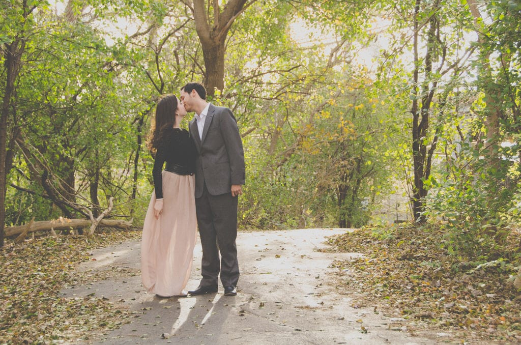 A young couple shares a kiss on a forest trail for their engagement shoot. The woman wears a flowy, pink chiffon maxi skirt with a black, leather waist belt.