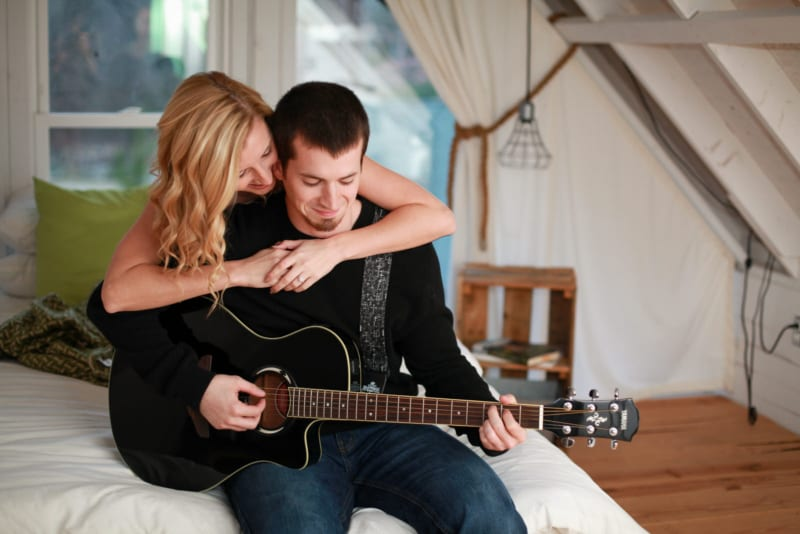 The couple is sitting on a bed while playing guitar.