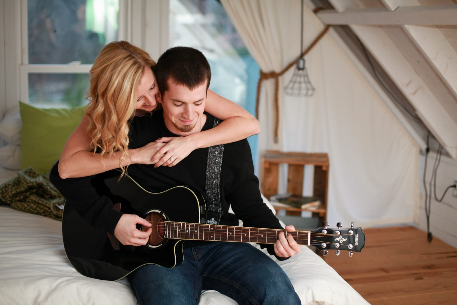Engagement Photography The couple is sitting on a bed while playing guitar.