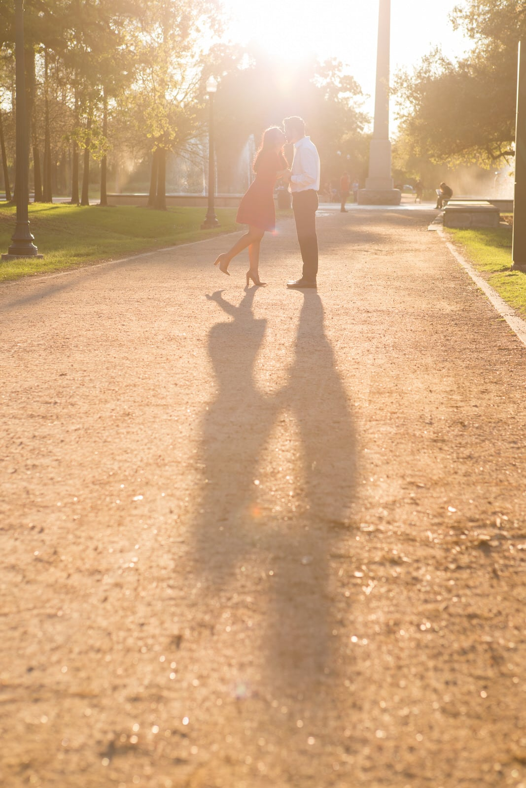 The couple is kissing as the sun is extending out their shadows.