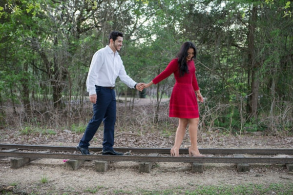 The couple is walking hand in hand over old train tracks.