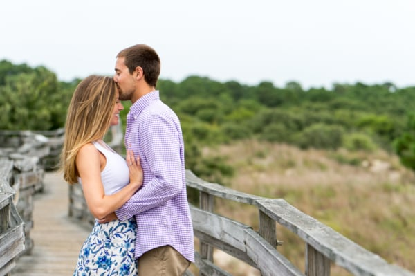 The couple is on a bridge leaning against each other and he is kissing her forehead.