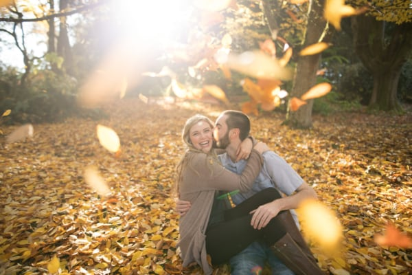 The couple is sitting on the forest floor in yellow/orange leaves while more leaves are falling down.