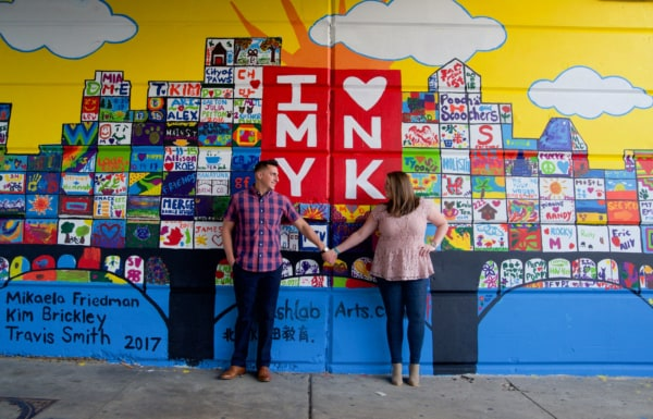 The couple is standing holding hands in front of a graphic wall.
