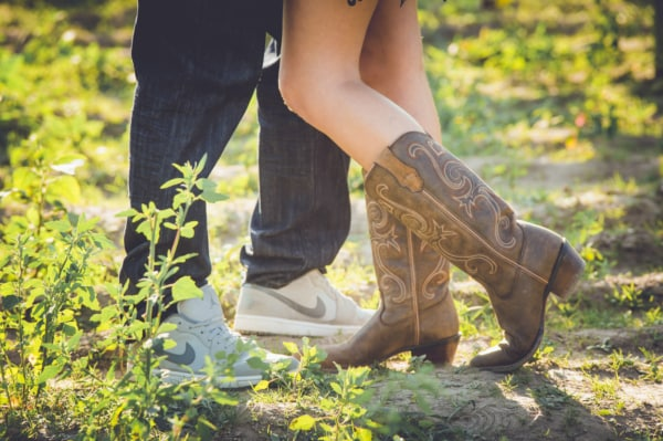 The couple's shoes while they are standing in a field.
