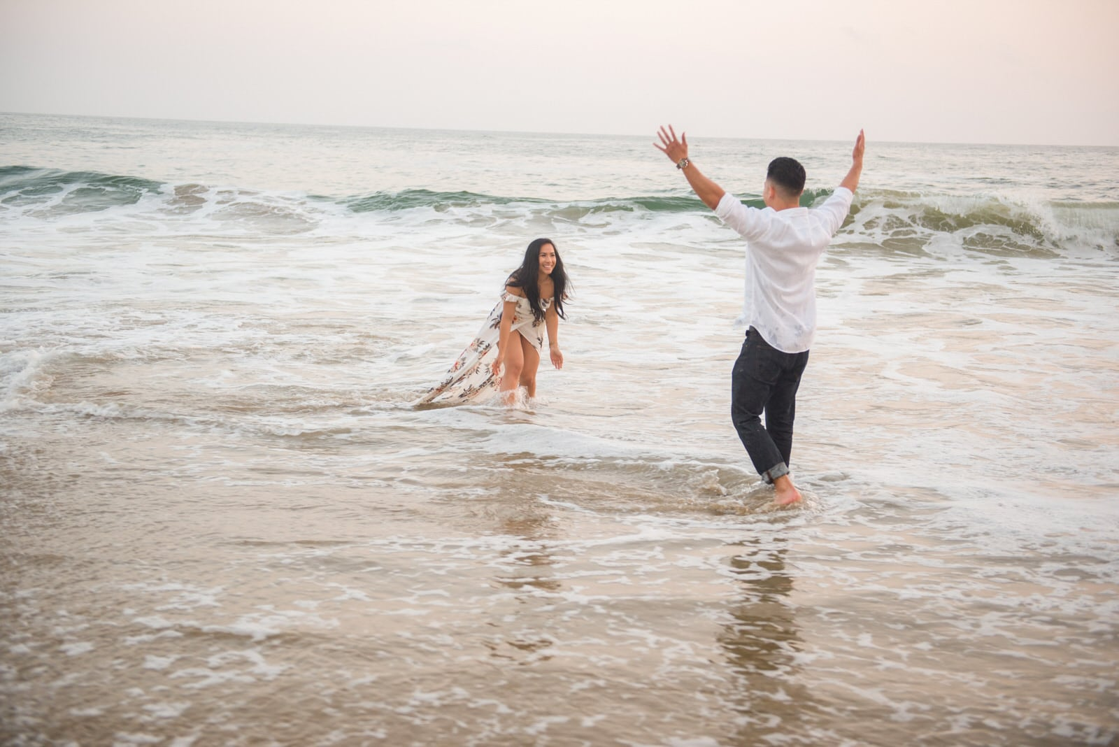The couple is walking through the water at the beach.