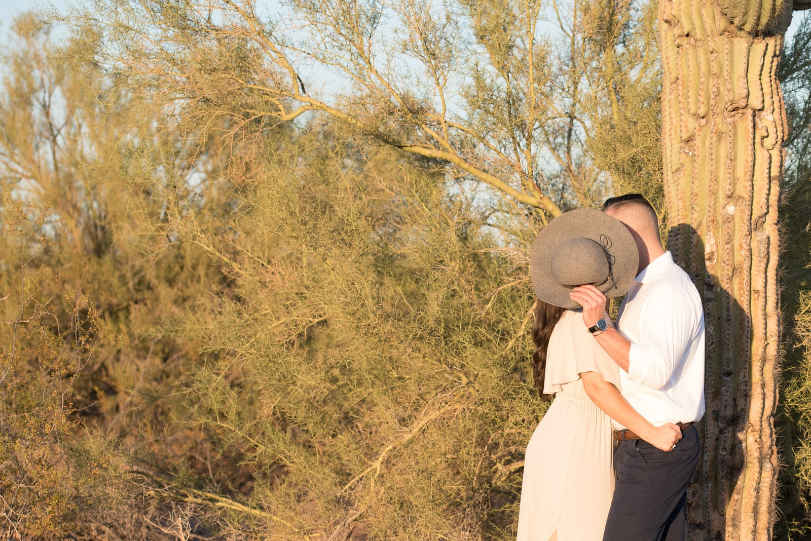 The couple is leaning against the cactus facing each other.