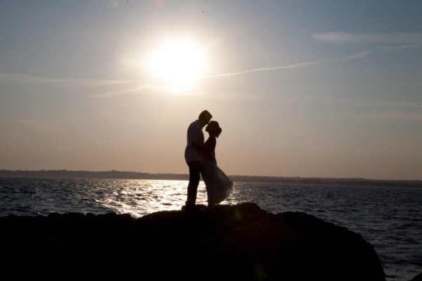 The couple is standing on a cliff by the ocean facing each other.