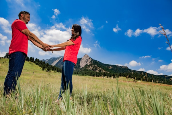 The couple is facing each other holding hands in front of Mountain formations.