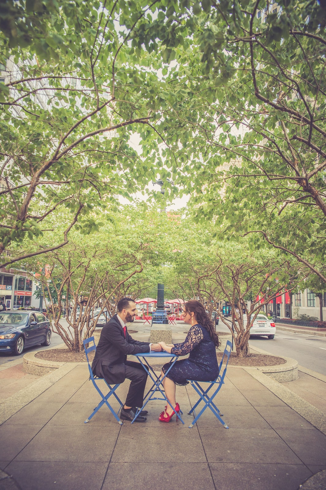 The couple is sitting at a table in downtown holding hands.