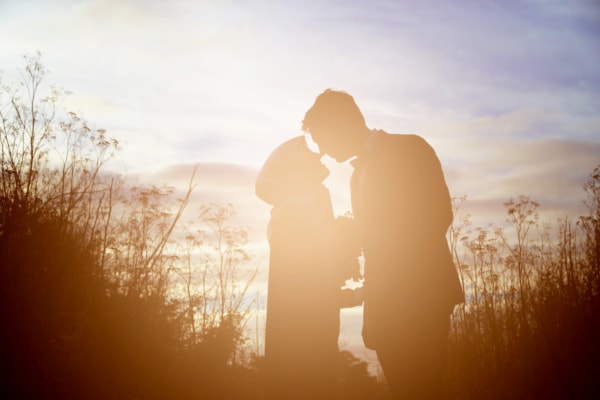 The couple is standing in a field facing each other being silhouetted by the sun.
