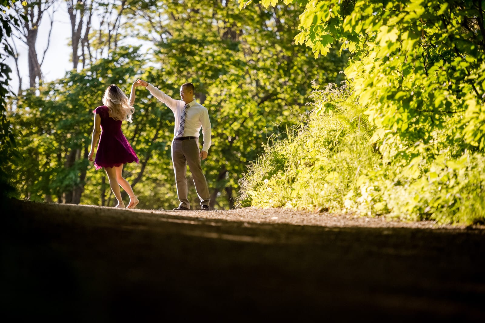 The couple is dancing in the sunlight on a forest path.