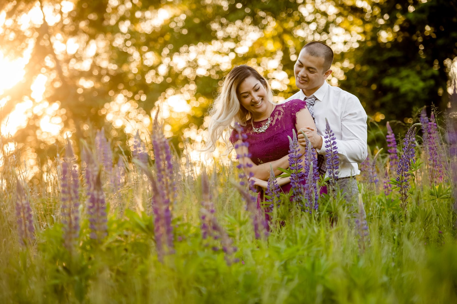 The couple is in a field of flowers.