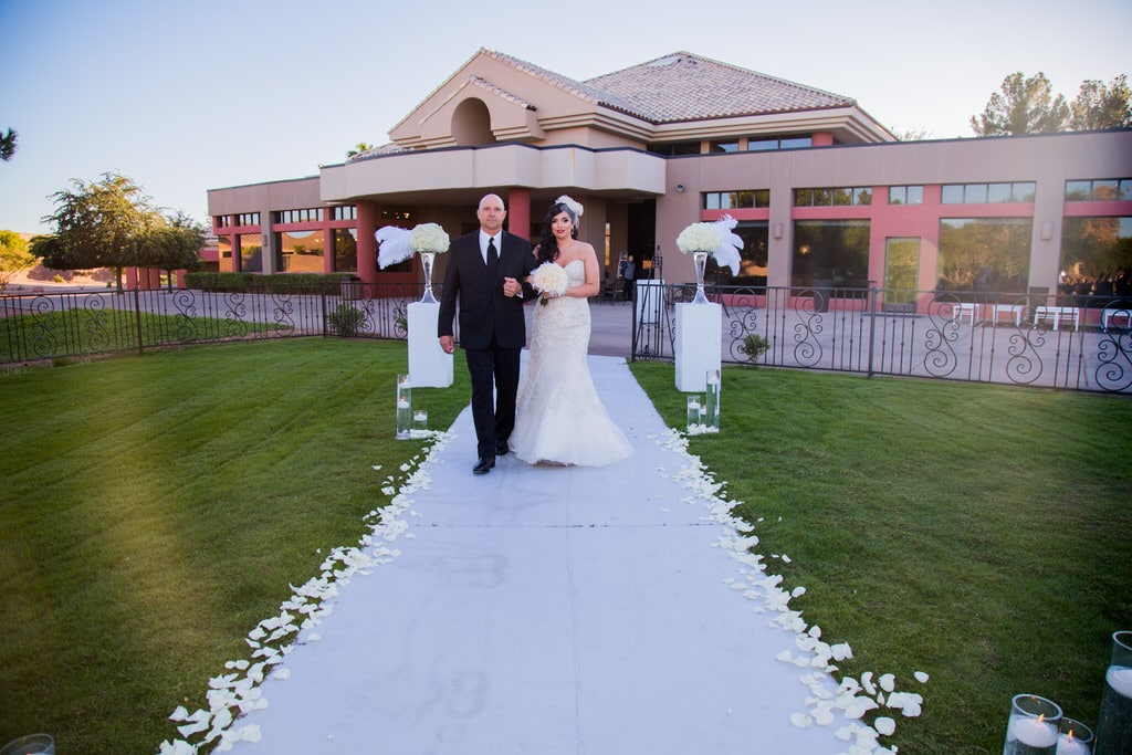 A father walks his daughter down the aisle lined with white rose petals. There are floating tea light candles placed in the entryway. She is carrying a white rose and feather bouquet and matching birdcage visor with netting.