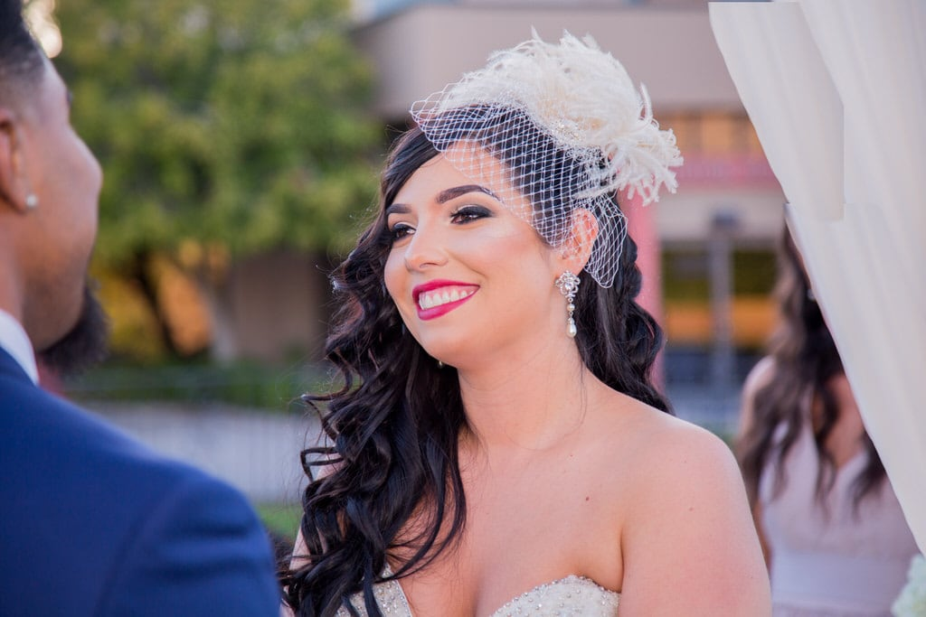 New Bride smiles adoringly at her new husband during the ceremony. The Bride wears an ivory, feathered birdcage visor with netting.