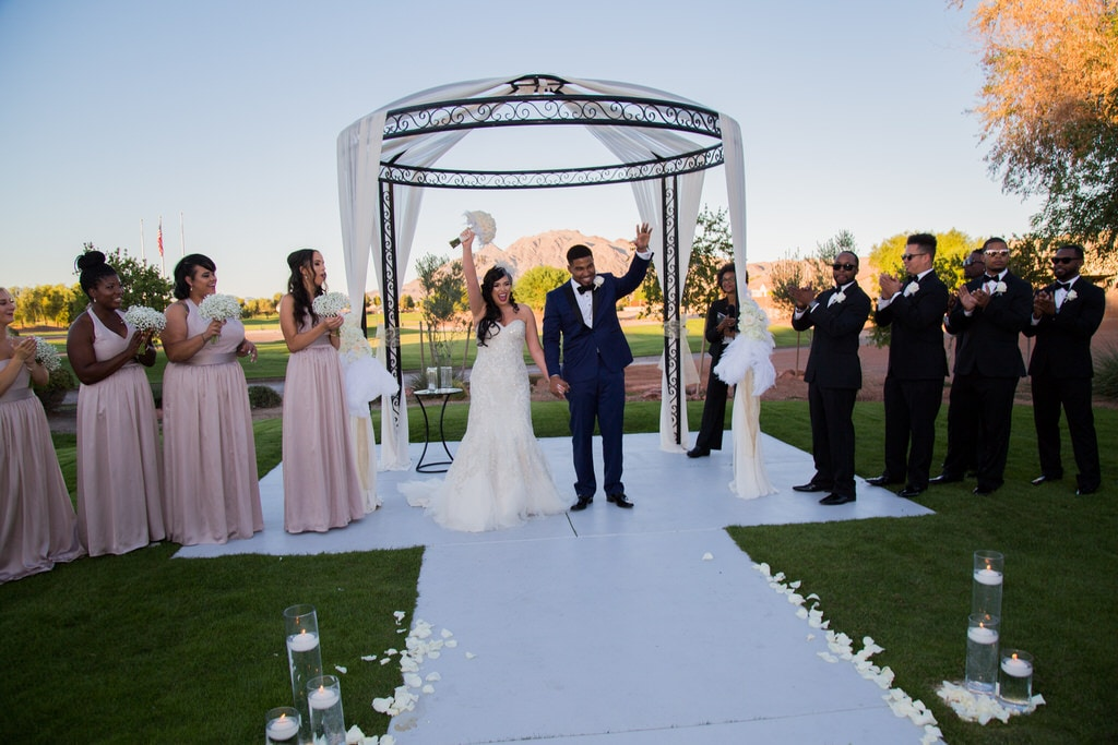Newlywed Bride and Groom conclude ceremony by raising their arms and greeting guests as husband and wife. Bridesmaids and Groomsmen clap and cheer on either side of the altar as the sun sets.