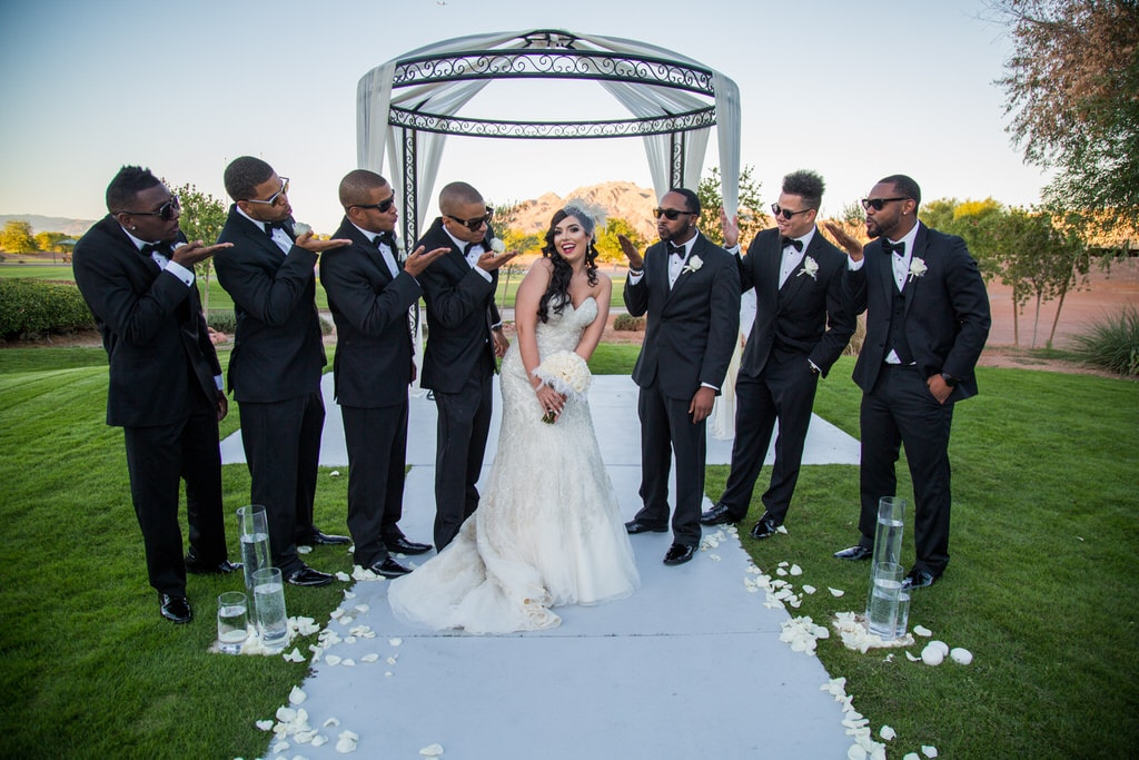 Bride and Groomsmen take a funny portrait photo. The Groomsmen wear sunglasses as they blow kisses at Bride while she poses sweetly, surrounded by ivory rose petals. Las Vegas wedding photography.