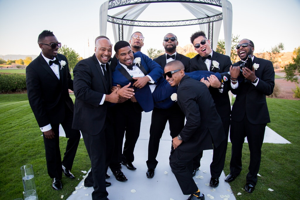 The charismatic groomsmen playfully lift the groom in the air while laughing and smiling for the wedding photographer. Beautiful iron gazebo rests behind them as the sun sets.