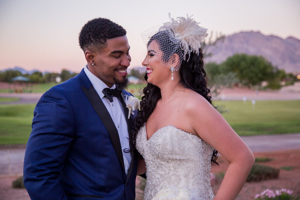 Fashion photographer captures a joyful moment between Bride and Groom at sunset. The Groom is wearing a handsome blue and black color block tuxedo jacket. The Bride is wearing a lovely vintage birdcage visor and drop pearl earrings.