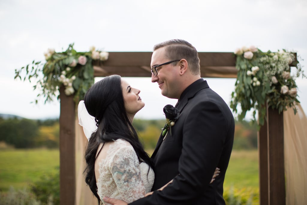 Rustic wedding photography. Bride and Groom embrace each other beneath a florally decorated atrium in an open field of wildflowers on an overcast day.