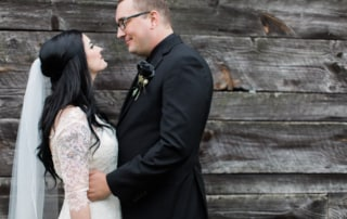 Bride and Groom look loving at one another posed in front of a rustic wooden cabin. The Groom is wearing a black rose boutonniere.
