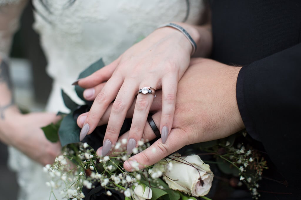 Newlyweds show off their rings and wedding bands resting atop the bride's bouquet. The bride has a stiletto manicure in a soft greige mauve.