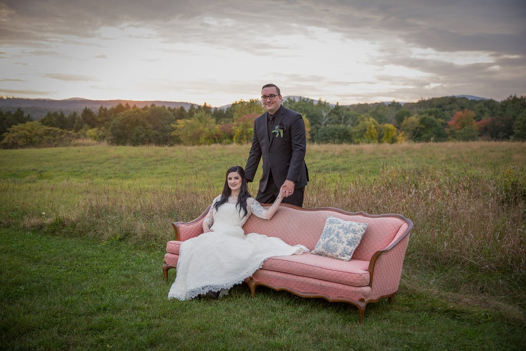 Vintage and rustic wedding photography of bride sitting on a pink couch in a grassy field as husband holds her hand from behind the couch.