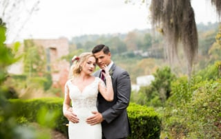 Bride and Groom give the photographer a sultry glance while in the garden. Greenery and old Willow trees rest in the background complimenting the Bride's floral hairpiece with deep red accents.