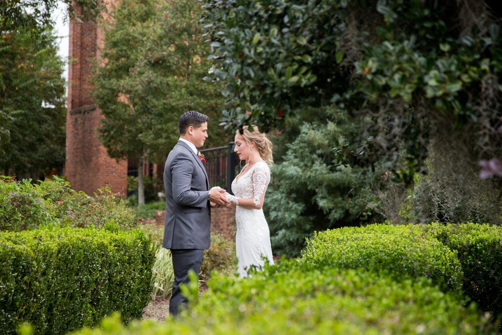 Candid photography of a Bride and Groom holding hands and exchanging words in the garden. Bushes, trees, and wildflowers surround them as they share a private moment.