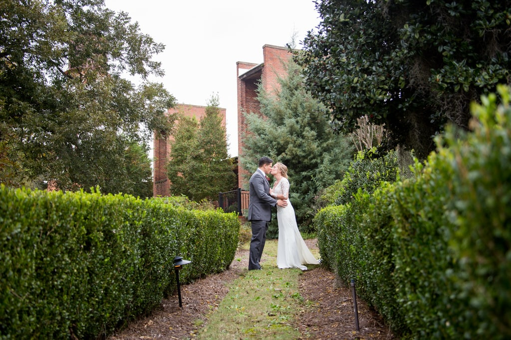 Newlywed Bride and Groom share a kiss at the entryway of a garden.