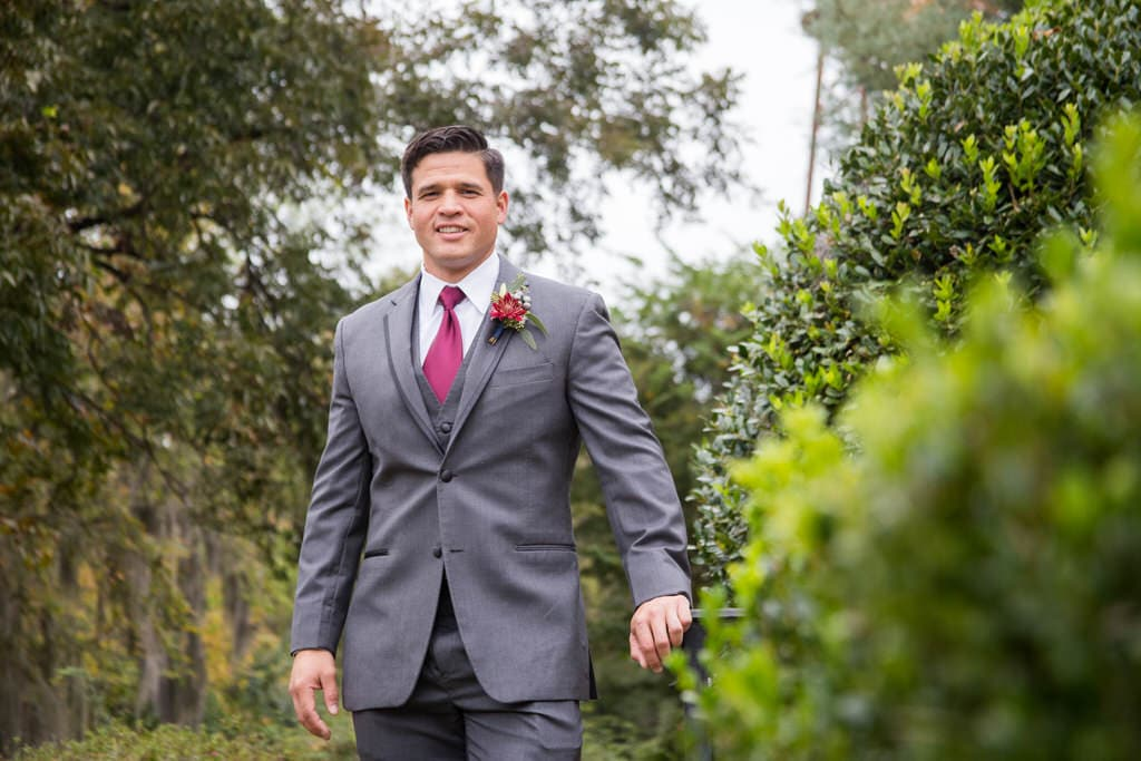 A handsome Groom sports a burgundy tie with a gray, three-piece suit and a smile. Trees and bushes cover the background as he prepares to marry.