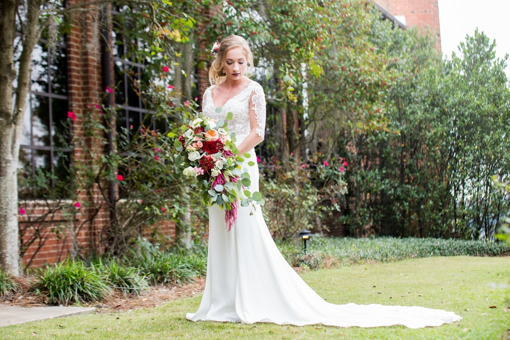 A gorgeous Bride carries her cascading bouquet on a stroll through the garden. The Bride is looking down, exposing her floral hairpiece and loose side-bun.