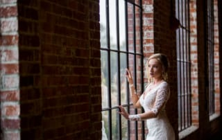 Fashion photographer captures a stunning shot of a Bride gazing out of a floor to ceiling window of an exposed brick loft. The bride has deep red lips and wears her hair in a loose and wavy updo with escaping tendrils.