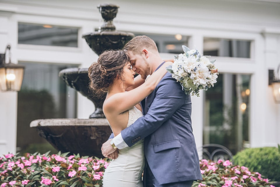 newlyweds embracing by fountain, photographed by Eivan's in Atlanta