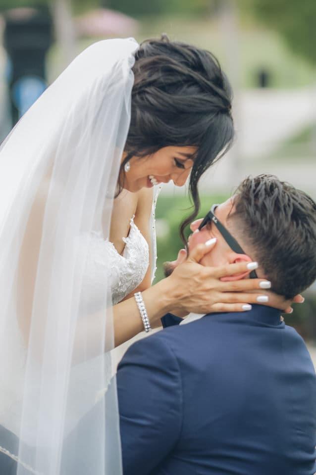 groom carries his bride after wedding ceremony