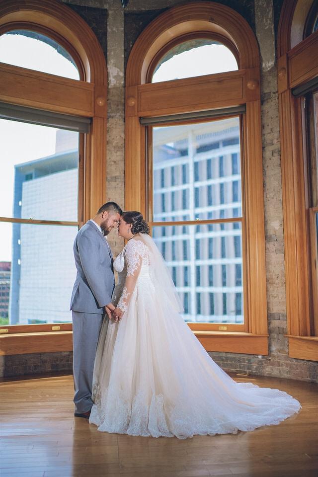 newlyweds posing in front of big windows, dallas wedding photographer portfolio
